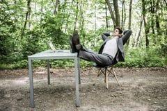 Großer Job Entspannter Geschäftsmann in der Klage mit Köpfen Unkosten und Beine auf Schreibtisch nach erfolgreicher Arbeit im grü stockfotos