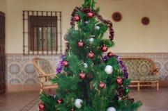 Großer künstlicher Weihnachtsbaum mit einigen dekorativen Bällen Stockfoto