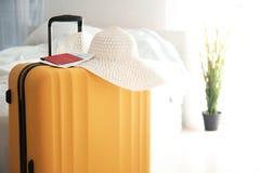 Großer Koffer, Hut und Dokumente zuhause lizenzfreie stockfotos