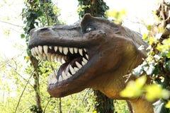 Großer Kopf eines Allosaurus-Dinosauriers am Wald Lizenzfreie Stockfotos