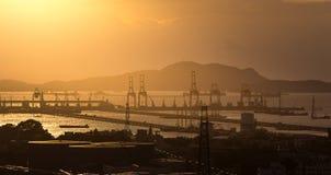 Großer Kran im Verschiffungshafen in der Sonnenuntergangzeit Lizenzfreies Stockbild