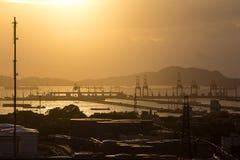 Großer Kran im Verschiffungshafen in der Sonnenuntergangzeit Stockfotografie