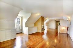 Großer langer Dachbodenraum mit Kamin. Leeren Sie sich mit goldenem Hartholz. Stockbild