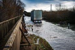 Großer LKW, der entlang überschwemmte Straße fährt Lizenzfreie Stockfotos