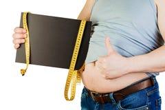 Großer männlicher Bauch, eine schwarze Platte mit Raum für Text auf whi halten Stockbild