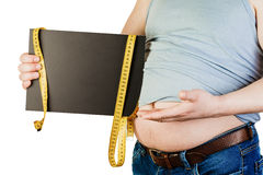 Großer männlicher Bauch, eine schwarze Platte mit Raum für Text auf whi halten Lizenzfreies Stockfoto