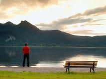 Großer Mann im roten T-Shirt an der Holzbank an Gebirgssee-Küste Dunkelheit bewölkt sich Lizenzfreies Stockfoto