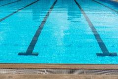 Großer olympischer GrößenSwimmingpool mit dem Laufen von Wegen Stockbild