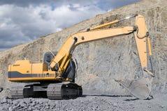 Großer Planierraupen-Exkavator mit Felsen lizenzfreie stockfotos