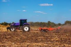 Großer purpurroter Traktor pflügt das Feld und entfernt die Überreste der vorher gemähten Sonnenblume lizenzfreies stockbild