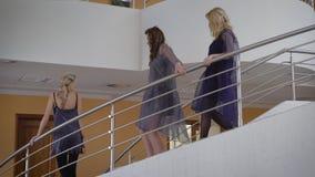 Großer Raum Drei Freundinnen in den Kleidern kommen unten Mädchen sind zu einer Partei bereit Die Blondine mit einer Borte in ein stock footage
