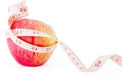 Großer reifer roter Apfel mit Maßband Stockbilder