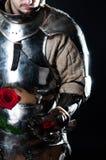 Großer Ritter, der schöne Blume betrachtet stockfotografie