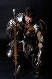 Großer Ritter, der seine Klinge und Sturzhelm anhält Stockfoto