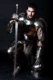 Großer Ritter, der seine Klinge und Sturzhelm anhält stockbild