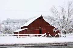 Großer roter Stall im Schnee. Stockfotos