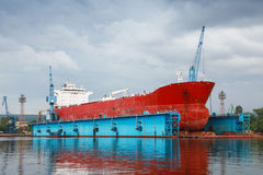 Großer roter Tanker unter der Reparatur im blauen Schwimmdock Lizenzfreie Stockbilder