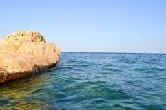Großer schöner gelber sandiger Felsen, ein Steinblock untergetaucht im Salzwasserseeblauen Wasser gegen den Himmel Stockbilder