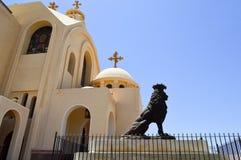 Großer schwarzer Steinlöwe auf dem Hintergrund einer ägyptischen orthodoxen weißen Kirche mit Kreuzen, Bögen, Hauben und Gebetsfe lizenzfreies stockbild