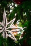 Großer silberner Stern verziert den grünen Weihnachtsbaum, der mit Unschärfescheinlichtern bedeckt wird Lizenzfreies Stockbild