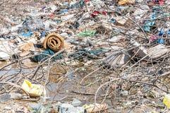 Großer Stapel des Abfalls und des Krams im Flusswasser, welches die Natur mit Sänfte verunreinigt Lizenzfreie Stockfotos
