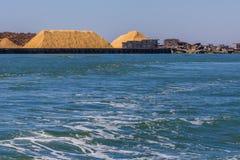 Großer Stapel des Sägemehls und der Klotz am Hafen lizenzfreie stockfotos