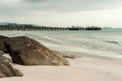 Großer Stein im Sand auf Strand mit Anlegestelle Lizenzfreies Stockbild