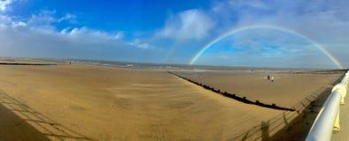 Großer Strand mit vollem Regenbogen Stockfotografie