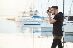 Großer Tag für das Photoshooting Kreativer und begabter junger Kameramann, der im Profil nahe Küste im Hafen während steht Lizenzfreies Stockfoto