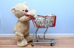 Großer Teddybär, der Geld im Einkaufswagen drückt Lizenzfreies Stockfoto