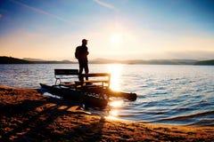 Großer Tourist mit Rucksackweg auf Strand am Tretboot im Sonnenuntergang Herbst in Meer Lizenzfreie Stockfotos