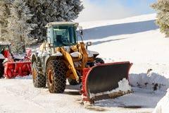 Großer Traktor mit Schneepflug während eines Winters Lizenzfreie Stockbilder