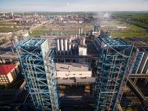 Großer Turm der Destillation zwei an der Raffinerie auf dem Hintergrund der Industrielandschaft Schattenbild des kauernden Geschä Stockbilder