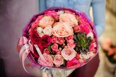 Großer und herrlicher rosa Blumenstrauß von Blumen mit einem Succulent in den Händen der Frau Lizenzfreie Stockfotografie