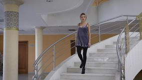 Großer und schöner Raum Das blonde Mädchen geht vorbildliche langsame Gangart auf einer Leiter Die Frau wird in einem kurzen Klei stock footage