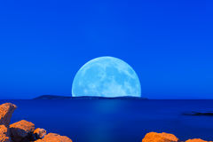 Großer Vollmond, der aus Drionisi-Insel in Griechenland herauskommt Blaue Stunde mit Felsen als Vordergrund Lizenzfreies Stockbild