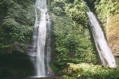 Großer Wasserfall und Frau in Bali Sekumpul-Wasserfall Stockfotografie