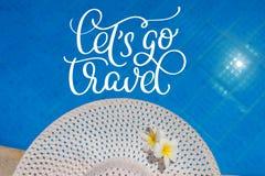 Großer weißer Hut am Rand des Pools und Text Lets gehen Reise Kalligraphiebeschriftungs-Handabgehobener betrag Stockfoto
