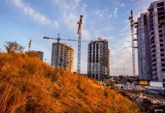 Großer zukünftiger Multispeichergebäudekomplex mit goldenem gelbem Gras des Herbstes im Sonnenunterganghimmel Lizenzfreies Stockfoto