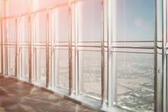 Großes Bürofenster mit einer Stadtansicht an einem sonnigen Tag mit klarem blauem Himmel lizenzfreie stockfotos