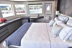 Großes Bett innerhalb des Bootes mit Kissen und drei Fenster- und kleinertür lizenzfreie stockfotos