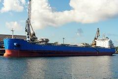 Gro?es blaues bulker Frachtschiff festgemacht im Frachthafen w?hrend der Frachtoperation lizenzfreie stockfotografie