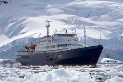 Großes blaues touristisches Schiff im antarktischen Wasser gegen den Hintergrund O Lizenzfreie Stockbilder