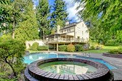 Großes braunes Haus außen mit Sommergarten mit Pool. Stockfoto