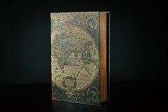 Großes Buch mit einer Abdeckungskarte der Welt stockfoto