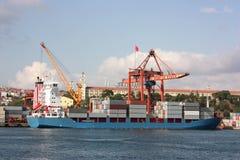 Großes Containerschiff in einem Dock am Kanal - Seitenansicht Stockbild