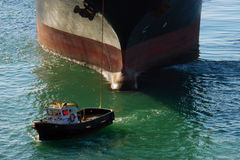 Großes Containerschiff im Hafen mit kleinem Boot in der Front Das enorme schwarze und rote Frachtboot folgen Liegeplatzservice-Bo Stockfotografie