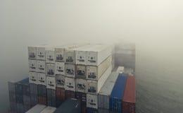 Großes Containerschiffschiff, das Nebel durchläuft Stockbilder