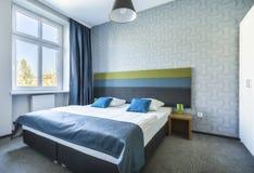 Großes Doppelbett in der blauen Hotelwohnung lizenzfreie stockbilder