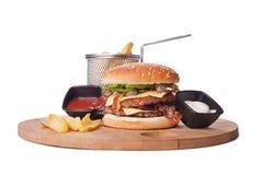 Großes Doppeltes briet Hamburger auf hölzerner Platte mit Ketschup und MA lizenzfreie stockfotos